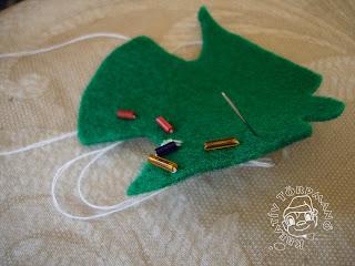Sz9veg: Gyöngysort is varrhattok rá! Kép: Zöld angyalkára felvarrt 5 szem szalmagyöngy (hosszúkásabb gyöngy). Még nincs befejezve, csak az egyik szárnyán van elkezdve.