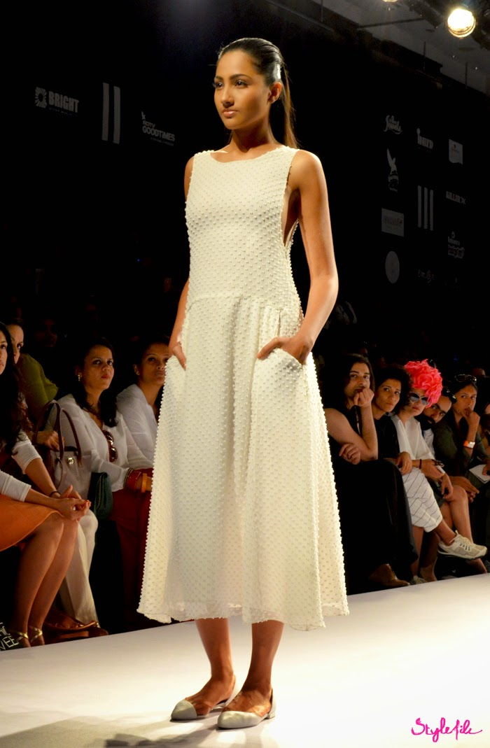 Model wears a white dress with buttis with a flowing silhouettes for Shift by Nimish Shah on runway at Lakme Fashion Week Summer Resort 2015