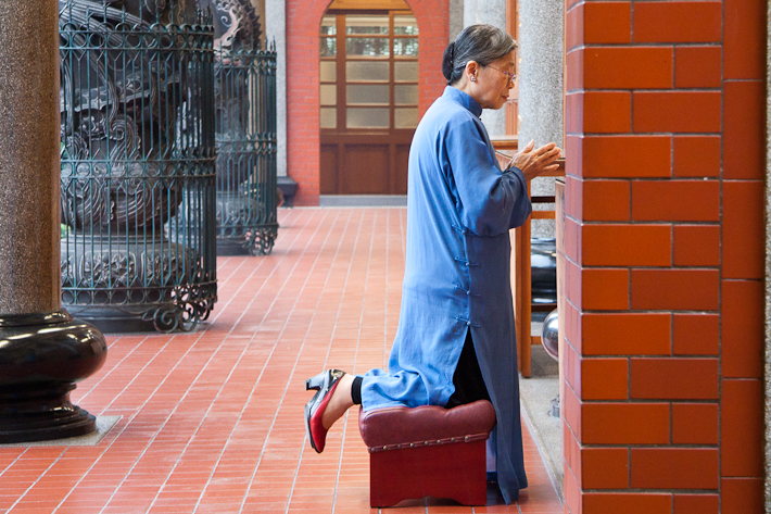 Woman praying at Xingtian Temple in Taipei