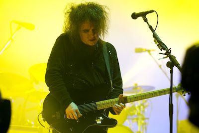 robert smith con su guitarra schecter ultracure con luces amarillas
