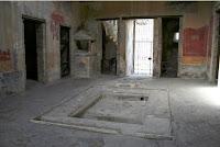Vista del atrio , con el   impluvium, el lararium y las puerta de entrada a las habitaciones  2 y 5