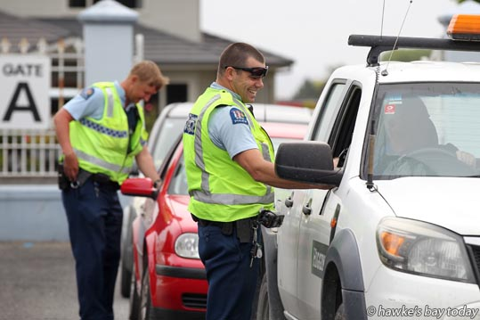 Front: Police acting sergeant Nic Renall breath-tests drivers in Market St, Hastings, after the Interislander Summer Festival Summer Races, at Hawke's Bay Racing, Hawke's Bay Racecourse, Hastings. photograph