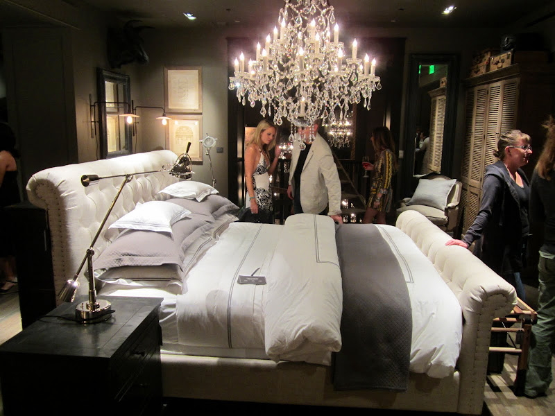 Bedroom in the new Restoration Hardware with a white tufted sleigh bed and grey and white bedding with a crystal chandelier hanging about it