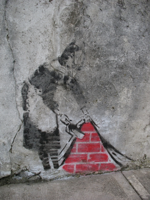 Banksy stencil art of maid holding dustpan lifting curtain revealing brick wall behind close up