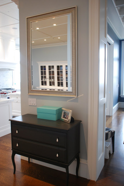 Ikea cabinet and mirror function as a morning launching pad for a busy family of 5.
