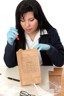 Crime scene investigator examines evidence in the lab.