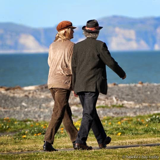 "L-R: Jan Fitzgerald, Leonard Lambert, Napier, married couple, well-known for walking hand-in-hand around Napier streets, pictured walking along the Rotary Pathway, Marine Parade, Napier, with Cape Kidnappers in the background. They both had a poem published in Random House's anthology ""Essential New Zealand Poems."" photograph"
