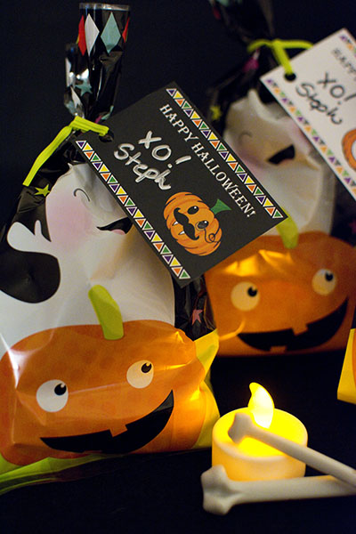 Halloween goody bags with pumpkins and ghosts on a black background lit by a tea candle with two crossbones