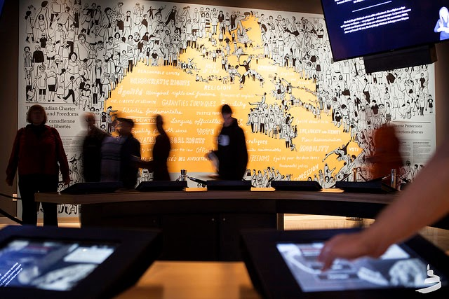 Visitors use touch screens in a gallery.