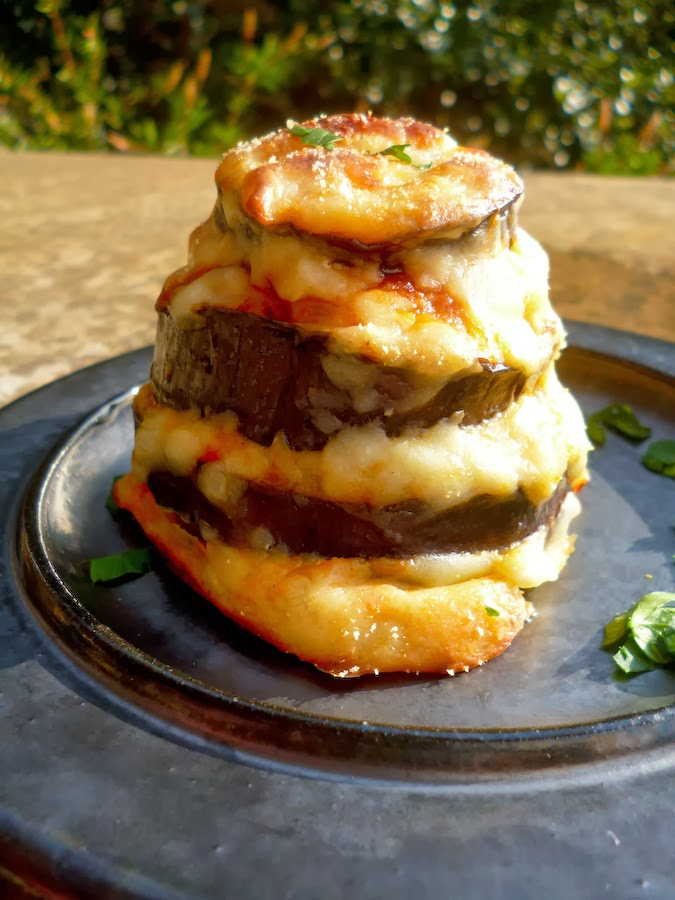 A black plate with a vegetarian moussaka mini tower
