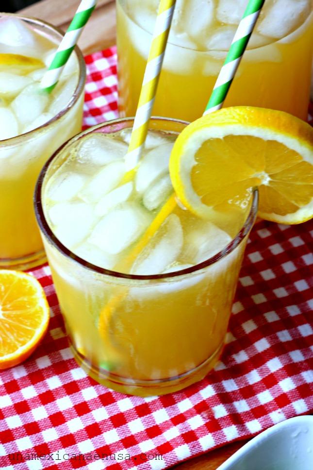 Dos vasos servidos con refresco de mandarina y hielo.