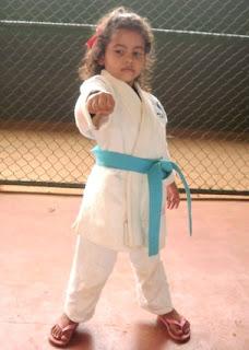 Início da descrição da imagem... Foto da Evellyn, de 5 anos de idade, vestida de kimono branco com a faixa azul, com o punho cerrado esticado para frente, demonstranto a técnica Maê Atê. Fim da descrição da imagem. Início da legenda...