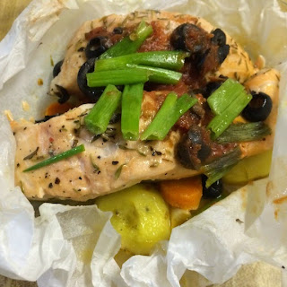 Salmon with carrots, potatoes and olives in parchment