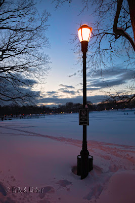 street light in snow silhouetted against pink and blue sunset