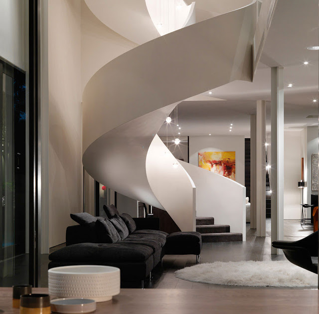 Modern living room with circular staircase at night