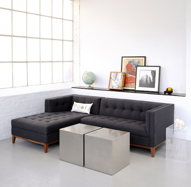 luxurious l shaped black fabric apartment size sofa on white polished concrete floor with some gray lacquered pouffes and small glass side table