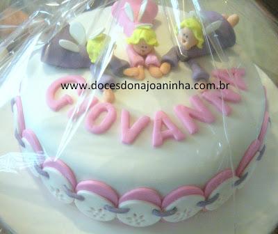 Bolo decorado Batizado Três Anjinhos voando de mãos dadas em rosa, branco e lilás com barrado em bordado inglês decorando a lateral do bolo.