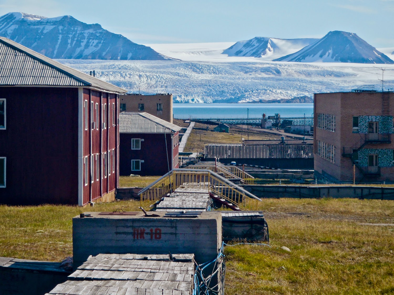 Instalaciones abandonadas en contraste con el glaciar Nordenskiöldbreen en Pyramiden