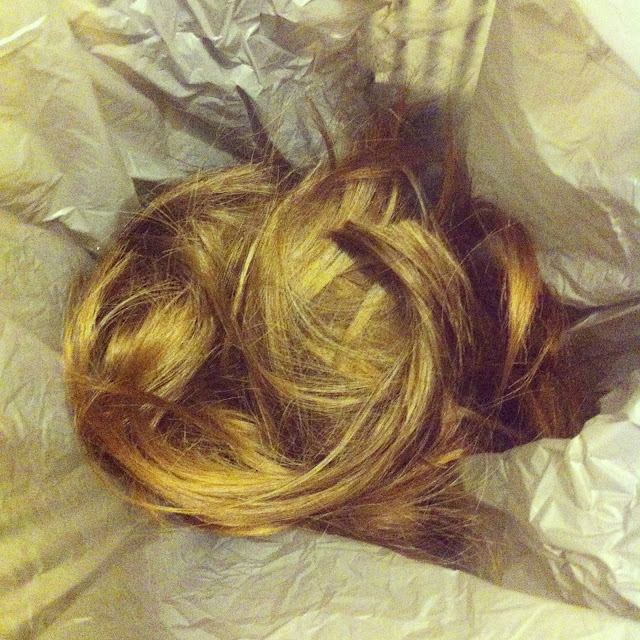 Photo of the hair I cut off inside a grey plastic shopping bag.