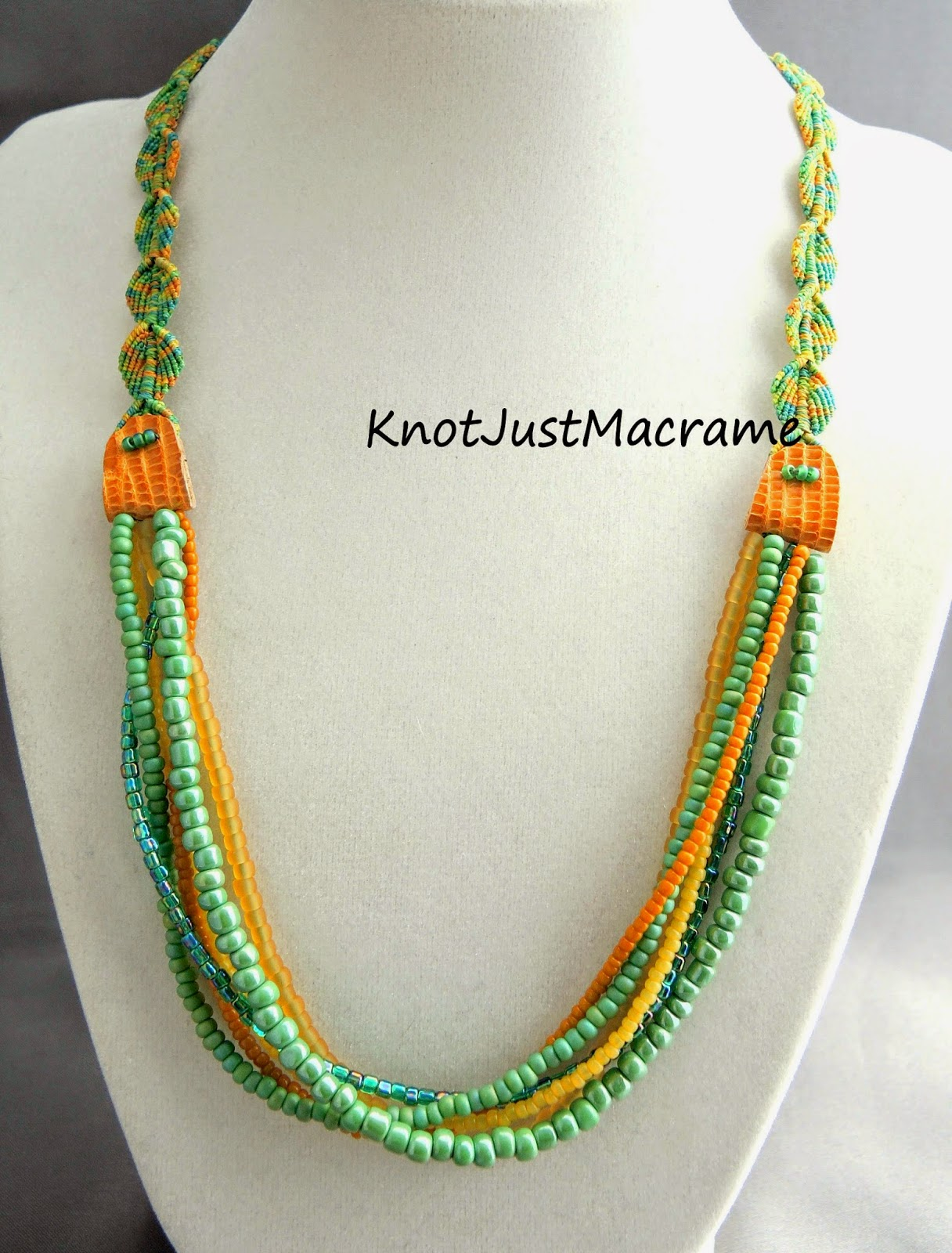 Micro macrame necklace by Sherri Stokey with knotted leaves, leather connectors and multiple strands of beads.