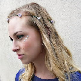 Jeweled cheeks and flowers in her hair.