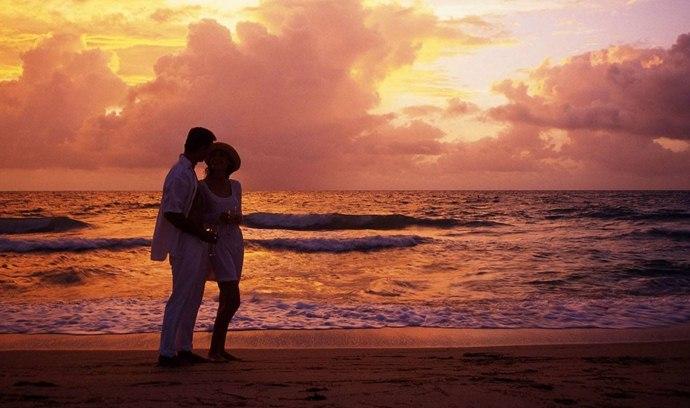 cuplu imbratisat pe plaja apus rasarit