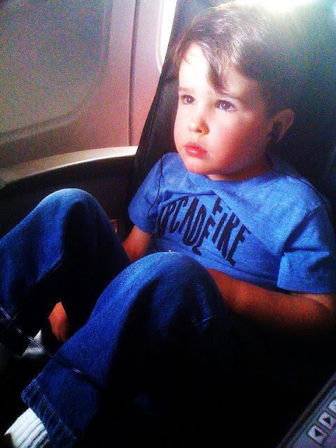 A kid wearing an Arcade Fire t-shirt watching cartoons on an airplane.