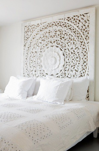 White bed with a beautiful carved panel headboard and eyelet bedspread