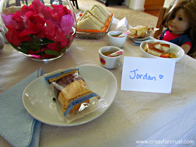 A wrapped cookie on a plate next to a place card, with a doll and food in the background.