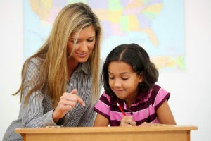 Image of a teacher and a student at a desk