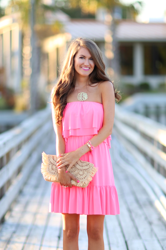 Pink ruffle dress with large monogram necklace