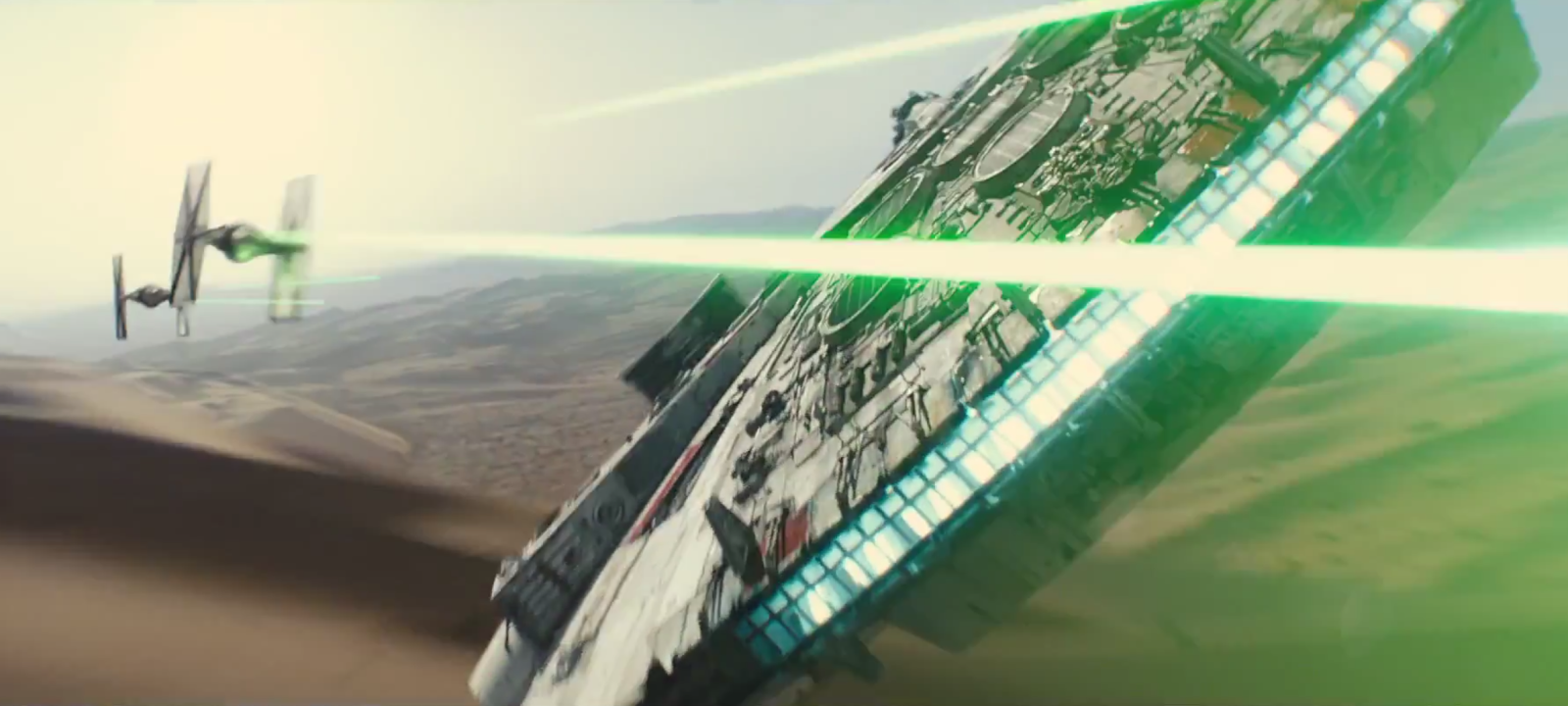 The millennium Falcon flying along the desert floor while engaged with Tie-fighters