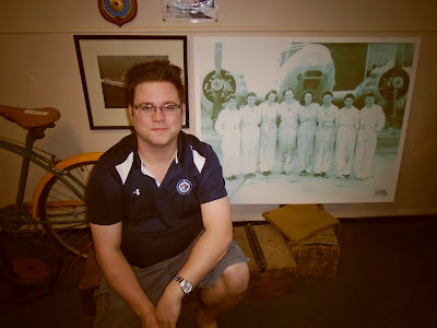 Former museum summer student poses with photograph