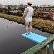 Um senhor sobre um trampolim azul, que parece estar próximo de saltar no rio Pinheiros