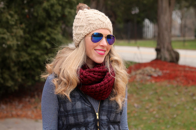 striped turtleneck layered under plaid vest with distressed jeans, and duck boots