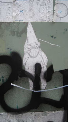 White wheat-pasted garden gnome on a green utility box with other graffiti nearby