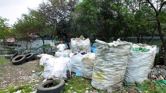 Maicon, jovem evangélico habitante de palafita na Zona Noroeste, complementa a renda da família com a venda do plástico coletado no estuário de Santos.