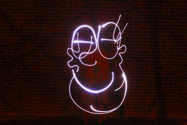 A big, goofy smiling face made by light painting onto a brick wall.