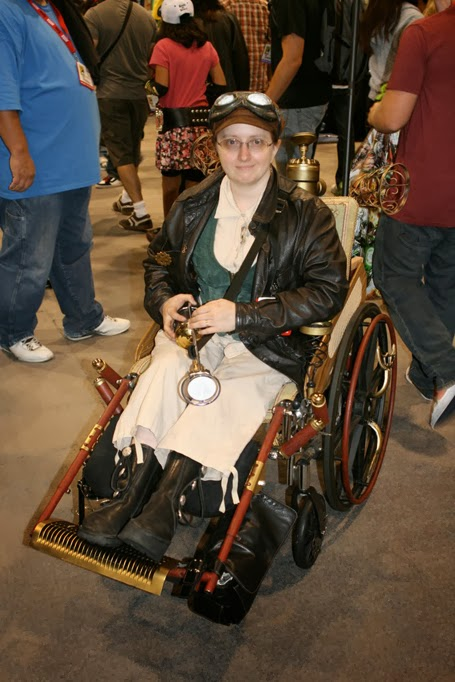 "Woman in wheelchair dressed in ""steampunk"" style, with wheelchair in the same style"