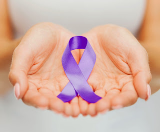A woman holds a purple ribbon in her hands.