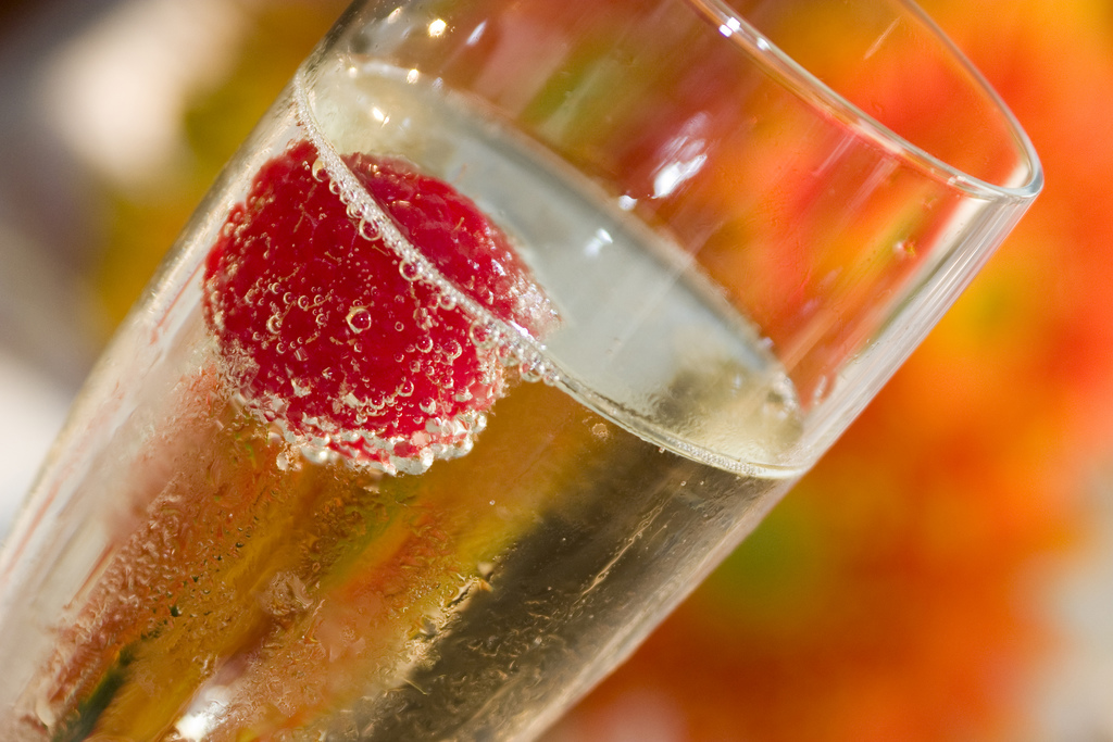 A closeup of a glass of champagne with a cherry