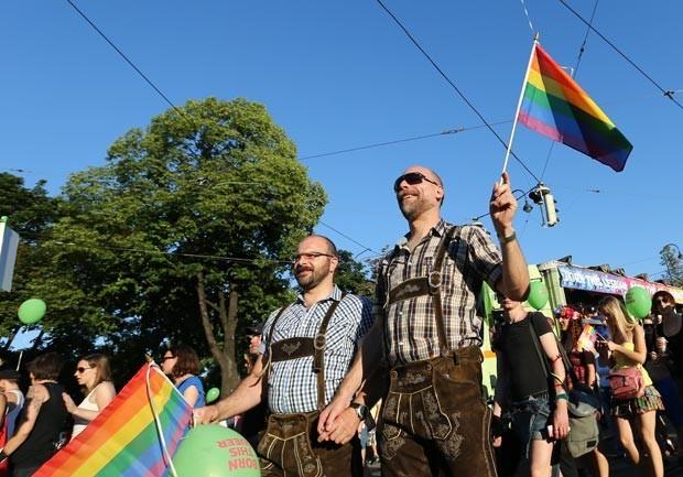 Homens vestidos com trajes tradicionais austríacos durante Parada LGBT em Viena, neste sábado (16) (Foto: Alexander Klein / AFP)