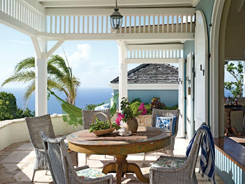 Beautiful coastal outdoor dining with weathered table and chairs and an ocean view