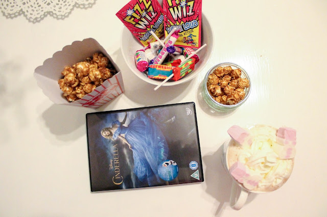 A night at the movies bundle Cinderella DVD, popcorn, retro sweets, hot chocolate with cream and marshmallows on white table.