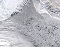 MODIS true-colour satellite image showing linear cloud patterns known as 'cloud streets' over the Greenland and Iceland Seas. These clouds are a signature of the transfer of heat and moisture that warms the atmosphere and cools the ocean resulting in a convective overturning of the water column, a process that plays an important role in the Atlantic Meridional Overturning Circulation. The island of Jan Mayen is in the center of the image and the flow around its topography results in the formation of spiraling cloud patterns known as 'von Karman vortices'. (Credit: GWK Moore) Click to Enlarge.