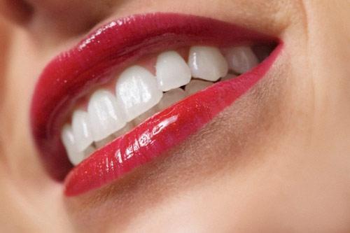 Pulizia della donna fra i suoi denti con una spazzola interdental