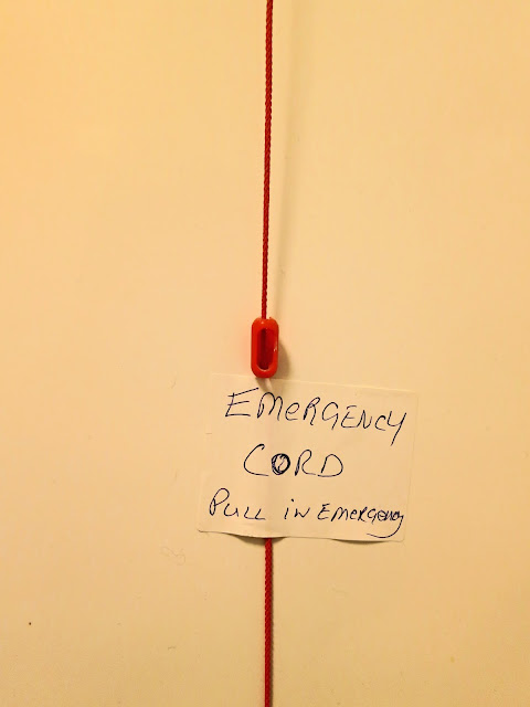 Red emergency cord with handwritten instructions - EMERGENCY CORD Pull in Emergency