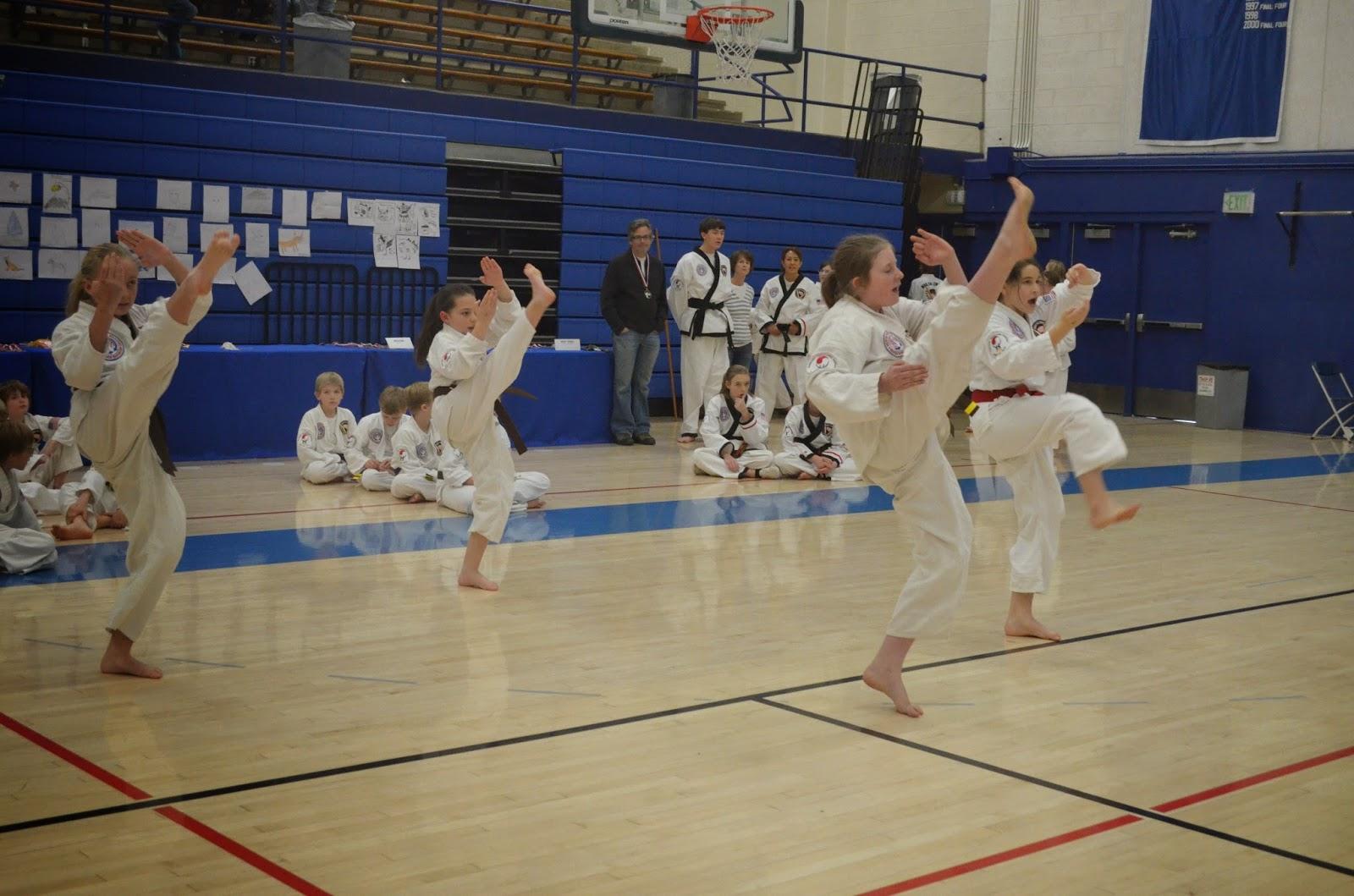 Martial art teen girls doing a front kick in unison