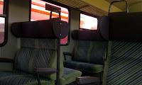 Bild: Zug, Zugabteil, Großraumabteil mit gegenüberliegenden Sitzen. Vor den Fenstern sieht man einen vorbeifahrenden Zug.