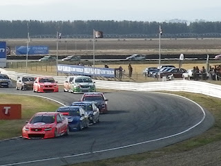 CARS RACING AROUND CORNER
